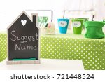 Small photo of Small chalkboard with text SUGGEST NAME on table at baby shower party