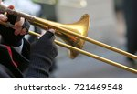 Small photo of hand of elderly man with gloves playing the trumpet in the music band during the sound performance