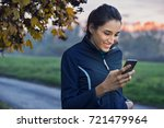 young athlete looking at phone... | Shutterstock . vector #721479964