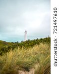 Small photo of Danish scandinavian lighthouse on the beach on dunes at blåvand billund with sand, Travel amd holiday