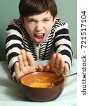 Small photo of preteen boy with disgust grimace refuse eating pumpking soup close up photo
