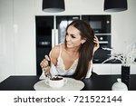 pretty brunette girl is eating...   Shutterstock . vector #721522144