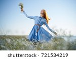 cheerful woman in a field with... | Shutterstock . vector #721534219