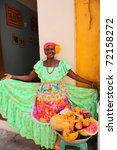 "CARTAGENA, COLOMBIA - JANUARY 14: ""Palenquera"" woman sells fruit on January 14, 2010 in Cartagena, Colombia. Palenqueras are an african descendant ethnic group found in the north of South America. - stock photo"