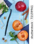 Ripe plums, spices and leaves of mint on blue wooden boards. - stock photo