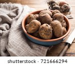 Small photo of Raw Organic potatoes in ceramic bowl on aged wood table with onion and garlic. Diet or cooking concept.Sele?tive focus.