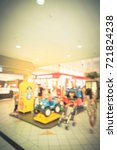 Small photo of Blurred kids enjoy riding electric toy car in shopping mall, Houston, Texas, US. Indoor game colorful electric powered sit ride for infant, toddler amusement park alike. Parent and child. Vintage tone