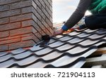 Small photo of Roofer builder worker attach metal sheet to the chimney. Unfinished roof construction.