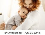 beautiful young mother tenderly ... | Shutterstock . vector #721921246