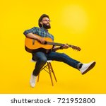 Handsome hipster musician man sitting and playing guitar.