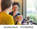 two women in a cafe smiling and ... | Shutterstock . vector #721960966