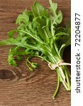 Bunch of fresh arugula leaves on a wooden table. - stock photo