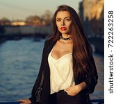 Small photo of Young attractive brunette woman with long hair and slightly ajar mouth, dressed in stylish white top and black jacket, standing on bridge and posing against river and city buildings on background.