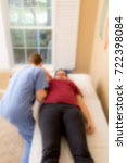 Small photo of Physical therapist performing an inferior glenohumeral glide on a patient.