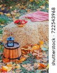 Small photo of Autumn decor hay, a basket of berries, a lamp, a perverted wooden bucket, autumn fruit