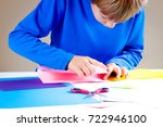 kid folding colored paper and... | Shutterstock . vector #722946100