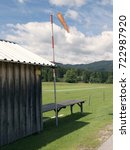 Small photo of Mountain small airport. Wind sleeve meter. Wooden cottage. Green lawn landing area. Travel destination for holidays. Mountain scenery near Salzburg. Hills in background, grassy pasture in foreground.