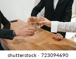 man clang glasses with whisky | Shutterstock . vector #723094690