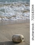 Small photo of Foam buoy on sand, the foaming sea waves washing ashore at the beach. Thailand