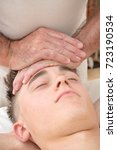 Teenage boy laying on a massage table, having a head massage - stock photo