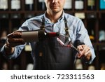 male sommelier pouring red wine ... | Shutterstock . vector #723311563