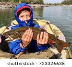 Small photo of Boy dressed for cold fishing on a lake in a float tube or pontoon, with a large trout fish (Brook Trout hybrid with Lake Trout, called Splake) he caught with a fly rod