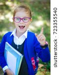 Small photo of A 7-year-old Years old girl Holding stack Books on she Hand and Smiling Talking