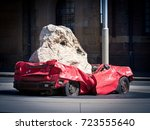 Small photo of Car crushed by a huge rock