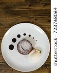 Small photo of chocolate fondant on a wooden background. with copy space. top view