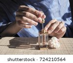 a woman opens the perfume oil.... | Shutterstock . vector #724210564