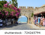 Small photo of RHODES, GREECE - AUGUST 2017: Ancient arch in old wall of Rhodes town with purple bougainvillea flowers in Rhodes town on Rhodes island, Greece