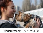 the girl is holding the dog in... | Shutterstock . vector #724298110