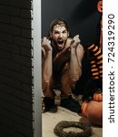 Small photo of Halloween man shouting with anger in black net pantyhose on head and hands on black wall. Pumpkins, striped stockings and wreath on floor. Autumn and harvest season. Holidays celebration concept