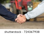 Small photo of Two farmers shaking hands in front of tractor on farm. Agribusiness concept