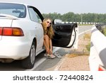 girl sits in the open car and dresses shoes - stock photo