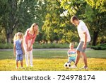 happy family playing football... | Shutterstock . vector #724978174