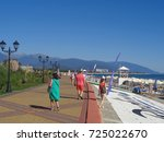 People walk along resort promenade, white umbrellas on the beach, blue sea and mountains on horizon, Sochi, Russia, September 9, 2017 - stock photo