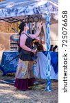 Small photo of July 30, 2017, Canterbury Renaissance Faire, Silverton, Oregon. A woman with fairy wings admiring a dream catcher in a booth.