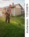 Small photo of Local homeownter uses a gas powered line trimmer to cut his lawn and edge the sidewalk.