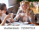 two laughing girls having tea... | Shutterstock . vector #725347513