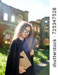 Small photo of Asian girl with book and magic stick wearing black warlock