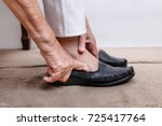 elderly woman putting on shoes | Shutterstock . vector #725417764