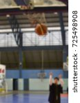 Small photo of A man is shooting a basketball in academic gown