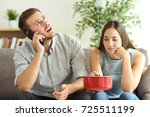 upset couple sitting in a couch ... | Shutterstock . vector #725511199