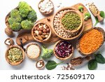 Stock photo vegan protein source beans lentils nuts broccoli spinach and seeds top view on white table 725609170