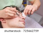 young man having face cleaned.... | Shutterstock . vector #725662759