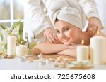 girl lying down on a massage bed | Shutterstock . vector #725675608