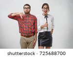 Small photo of Displeased funny nerd shows thumb down, has sulk expression, stands next to happy female model who expresses opposite emotions, being glad and agree with something. Body language and lifestyle