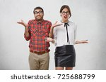 Small photo of Indoor shot of uncertain man and woman in formal clothes shrug shoulders, don`t know answer or way out, look displeased and dissatisfied. Two smart students don`t understand difficult material