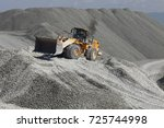 Small photo of Heavy wheel loader excavator against the background of gravel hills. Quarry equipment. Mining industry.